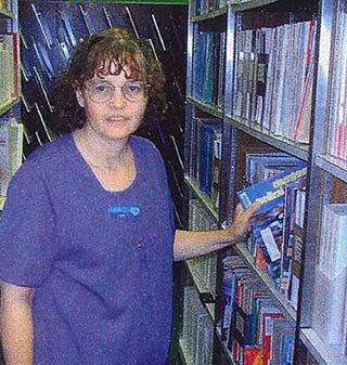 In this historic photo, Nebraska Methodist College Library Assistant Tem Adair checks the stacks.