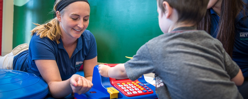 Photo of an NMC OT student at work in the pediatrics lab