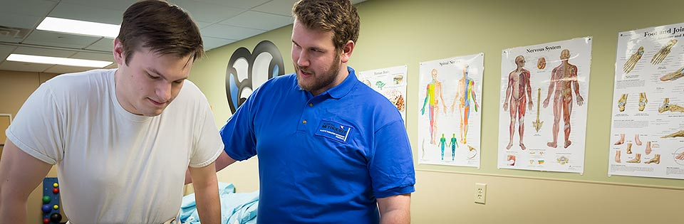 A Physical Therapist Assistant student at NMC works with a volunteer client.